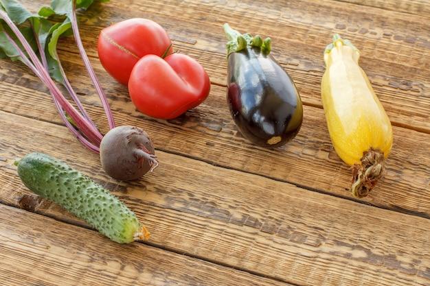 Acabei de colher tomates, beterraba, pepino, berinjela e abóbora em velhas tábuas de madeira. apenas vegetais colhidos. vista do topo.