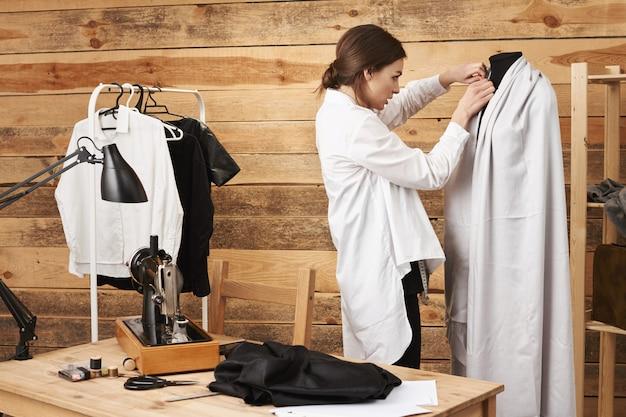 Acabei de colocar um alfinete aqui e pronto. jovem talentosa e criativa alfaiate, colocando as roupas que costurou no manequim enquanto a alcançava com a máquina de costura em sua oficina. um dia sua marca se tornou famosa