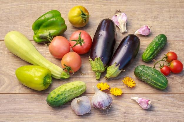 Acabei de escolher abobrinha, tomate, pimentão, berinjela, alho e pepino na placa de madeira. apenas vegetais colhidos. vista do topo