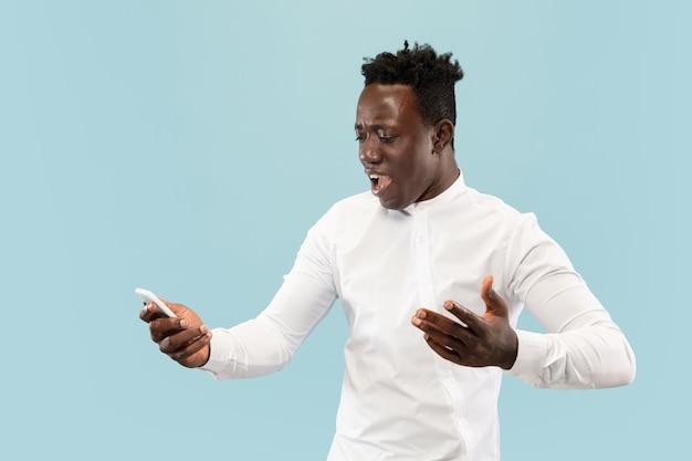 Acabei de perder uma aposta. jovem afro-americano com smartphone isolado em estúdio azul