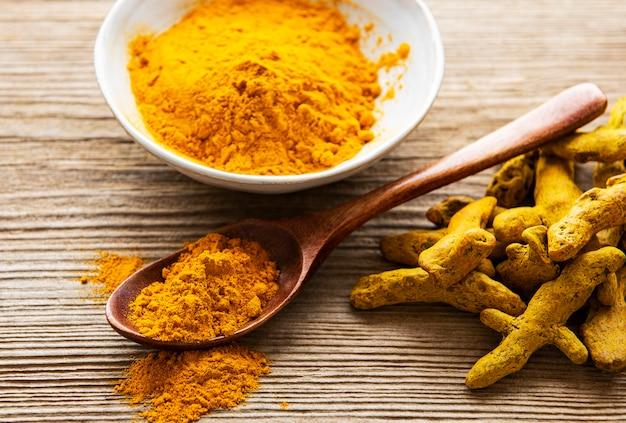 Açafrão amarelo em pó e raízes secas na mesa de madeira.