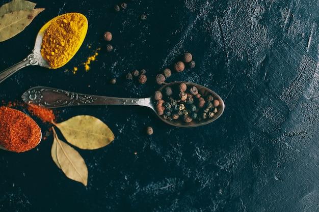 Açafrão e pimentão de pimenta preta mentem sobre um fundo escuro