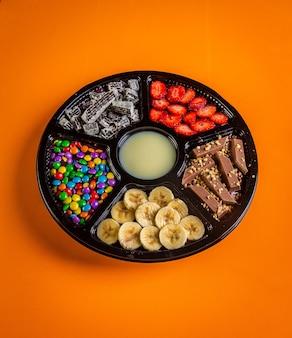 Açaí congelado com banana, granola, chocolate e bombons para compartilhar.