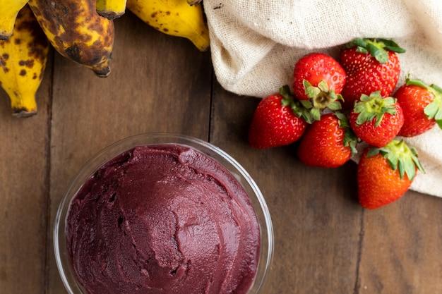 Açaí, tigela de sorvete de açaí congelado brasileiro. com frutas na mesa de madeira. vista superior do menu de verão