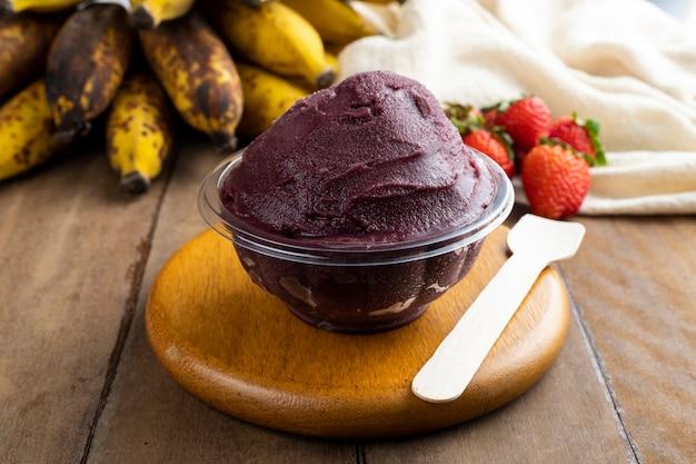 Açaí, tigela de sorvete de açaí congelado brasileiro com morango e banana. com frutas na mesa de madeira. vista frontal do menu de verão