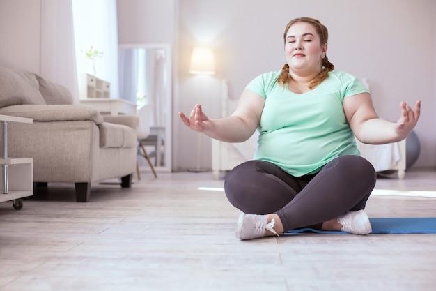 Acalmar. mulher ruiva calma com tranças francesas acalmando a respiração enquanto faz exercícios respiratórios