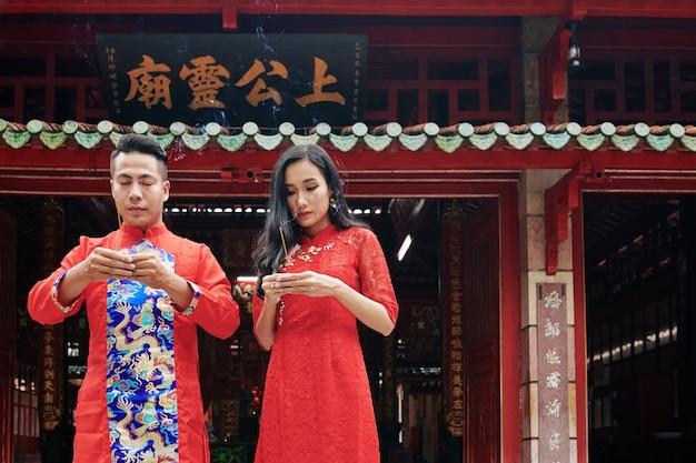Acalme jovens vietnamitas sérios queimando incensos durante a celebração do ano novo lunar em templo budista