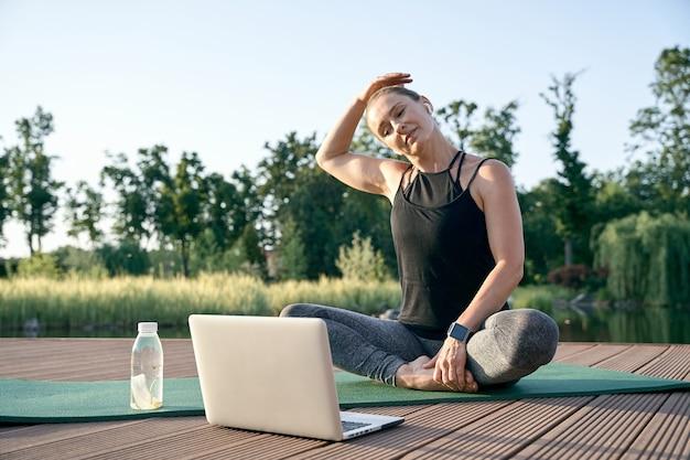 Acalme sua mente atlética bela mulher de meia-idade assistindo a vídeos instrutivos em um laptop enquanto