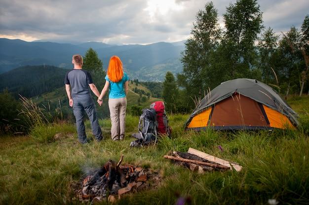 Acampamento. amando o casal em pé perto do fogo, mochilas e barraca