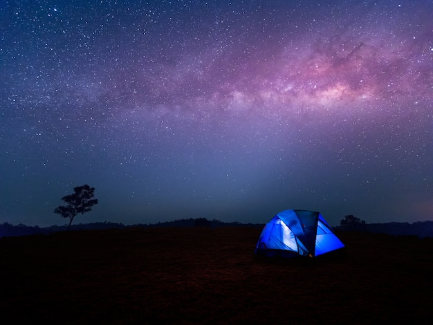 Acampamento. barraca azul brilha sob um céu noturno com a via láctea.