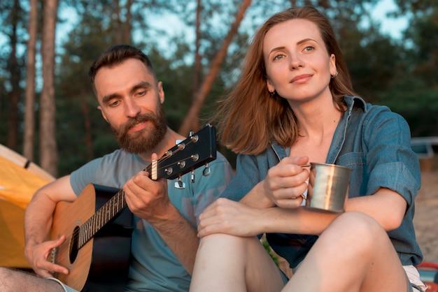 Acampamento casal curtindo a música