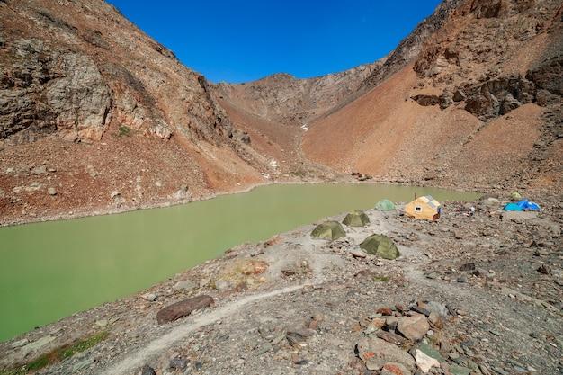 Acampamento de trânsito perto de um lago de montanha no caminho para o topo da geleira bolshoy aktru, altai, rússia.