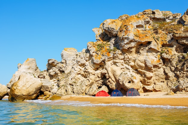 Acampamento de três tendas em uma praia selvagem de areia