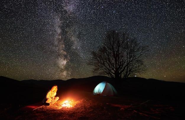 Acampamento noturno. caminhante descansando perto da fogueira sob o céu estrelado