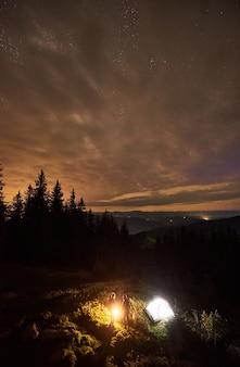 Acampamento noturno com pessoas ao redor da fogueira sob o céu estrelado
