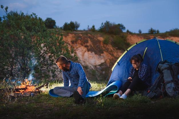 Acampamento noturno nas montanhas feliz casal de viajantes sentados ao lado da fogueira e da tenda turística brilhante