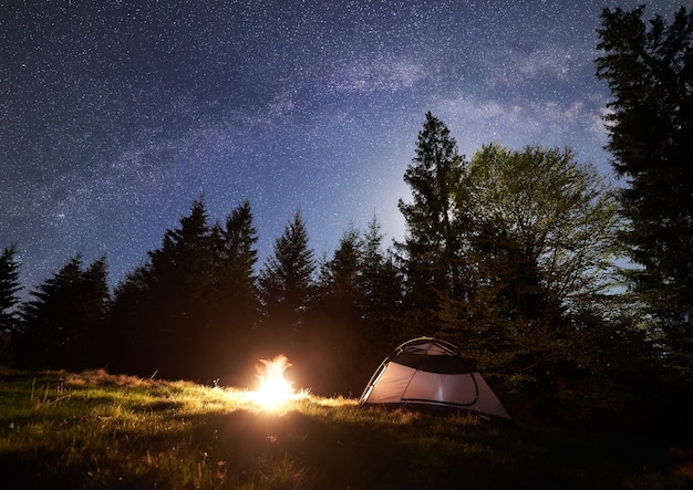 Acampamento noturno nas montanhas sob o céu estrelado e a via láctea