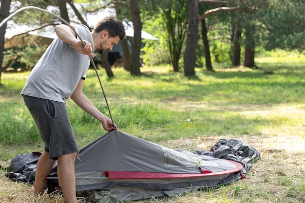 Acampamento, viagens, turismo, conceito de caminhada - jovem montando uma barraca ao ar livre.