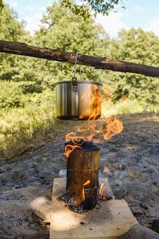 Acampando, uma panela com água ferve sobre o fogo.