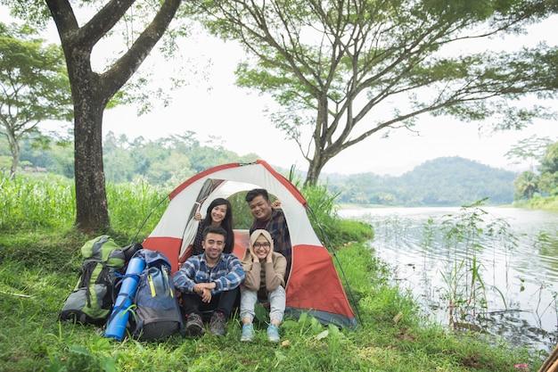 Acampar à beira de um lago com amigos