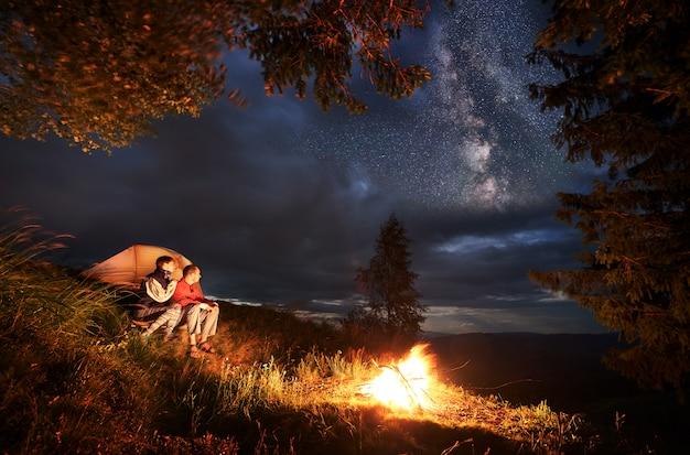 Acampar à noite. jovem casal caminhantes sentado junto à fogueira e tenda laranja iluminada, olhando para a distância sob o céu da noite. através das nuvens no céu são visíveis estrelas brilhantes.