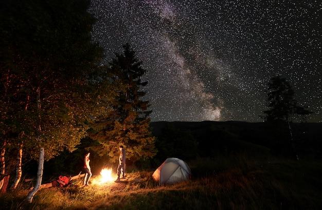 Acampar à noite. um cara e uma garota de pé junto à lareira perto da floresta e tendas sob o céu estrelado