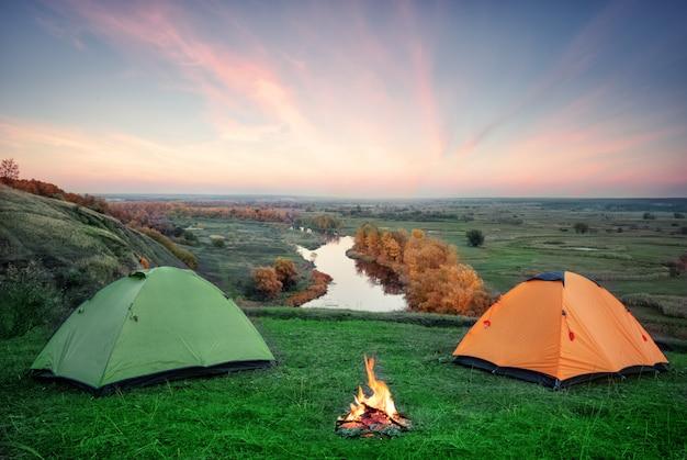 Acampar de tendas laranja e verdes com fogo nas margens do rio