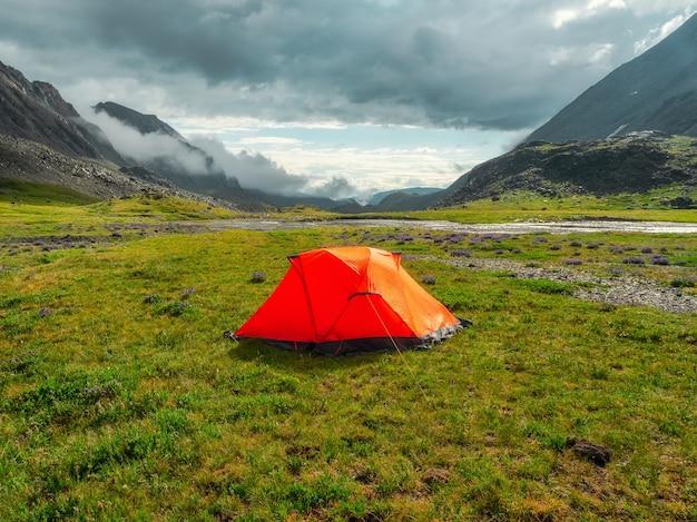 Acampar em um planalto de alta altitude verde de verão. tenda laranja depois da chuva. paz e relaxamento na natureza.