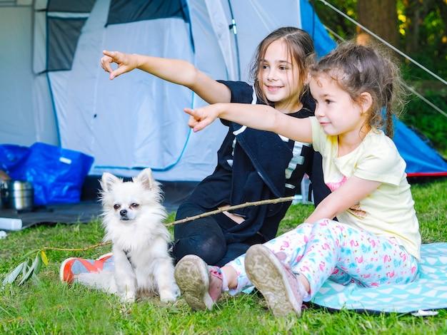 Acampe na barraca - meninas com um cachorro chihuahua sentadas juntas perto da barraca.