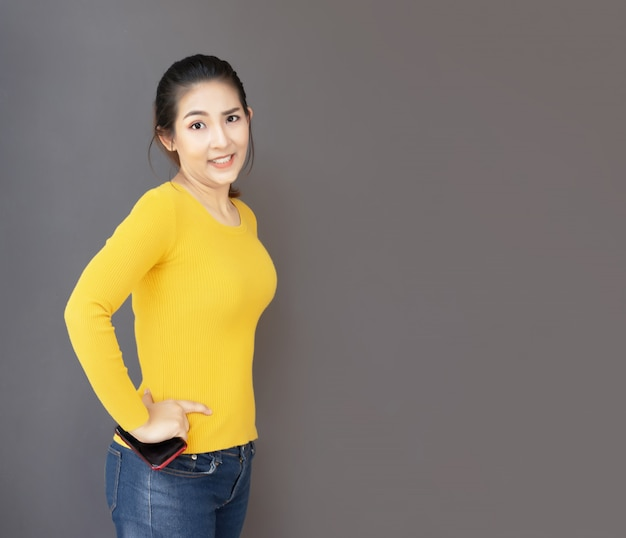 Ação asiática de mulher de retrato bonito com camisa amarela casual