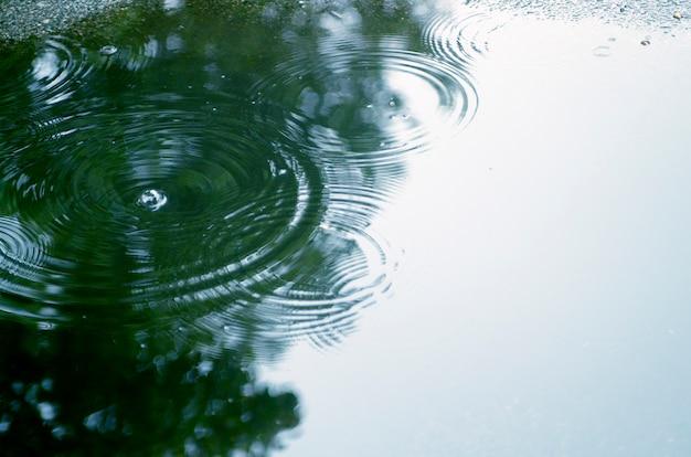Ação de efeito cascata de chuva cai reflexo na água. círculos de água concêntricos diferentes