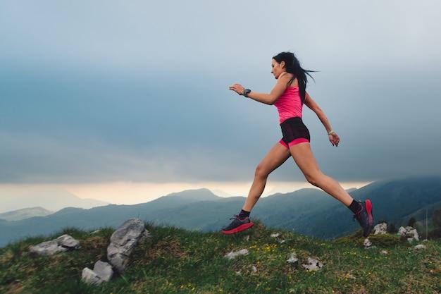 Ação de mulher desportiva com corpo atlético durante uma corrida de natureza