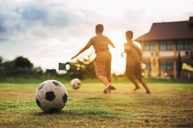Ação esporte ao ar livre de crianças se divertindo jogando futebol