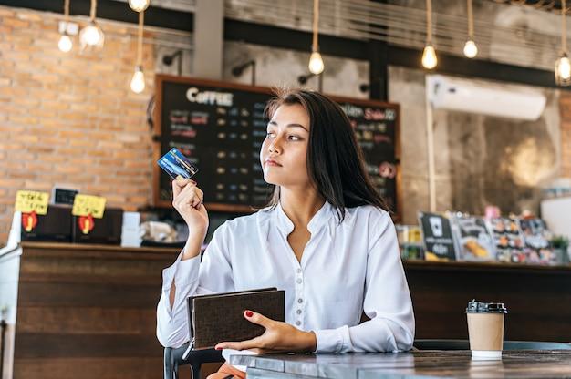 Aceitar cartões de crédito de uma bolsa marrom para pagar mercadorias em pedidos de café.