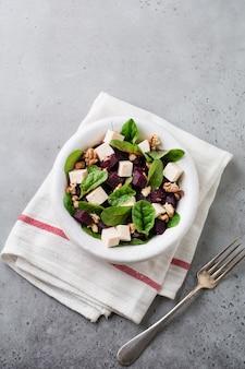 Acelga, rúcula, beterraba, queijo ricota e salada de nozes com azeite de oliva em um prato de cerâmica sobre uma superfície de concreto cinza