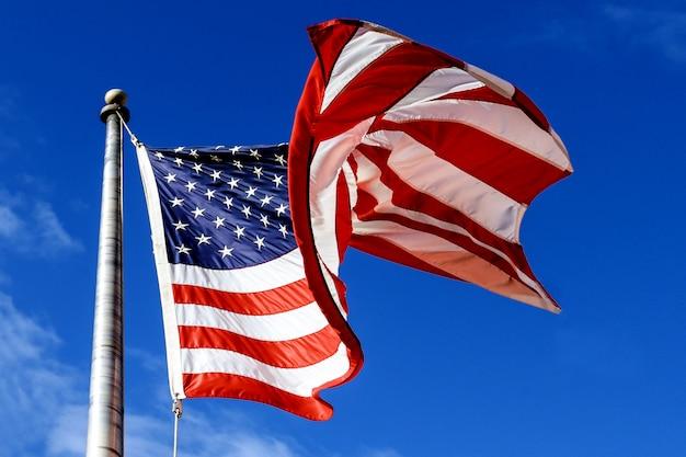 Acenando a bandeira americana no céu azul