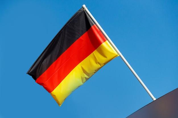 Acenando a bandeira da alemanha em um mastro contra um céu azul