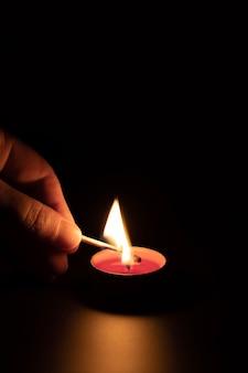 Acendendo uma vela vermelha com um fósforo no escuro