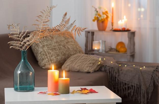 Acendendo velas com decoração de outono na mesa branca em casa