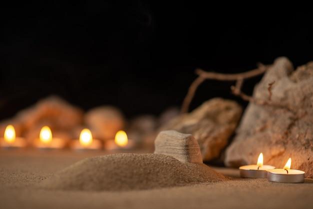 Acendendo velas com pedras ao redor da pequena sepultura como memória funeral de morte