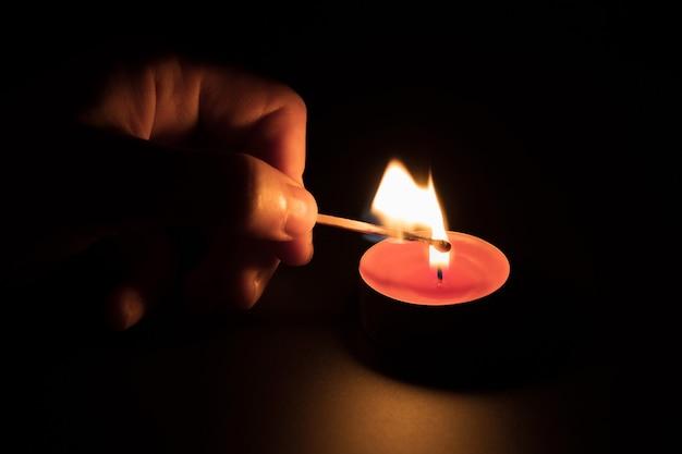 Acender uma vela vermelha com um fósforo no escuro. conceito de memória. fundo preto.