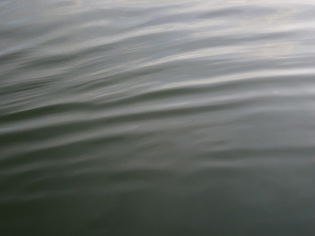 Acene a textura no rio com nuvens refletindo na superfície da água.