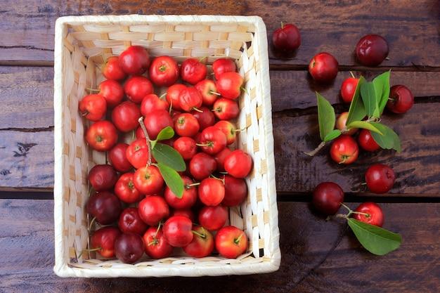 Acerola cereja cru, fresco, caixa na mesa de madeira rústica, frutas antioxidantes
