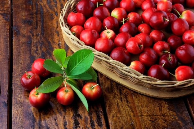 Acerola cereja crua, fresca, na cesta com forma de coração na mesa de madeira rústica