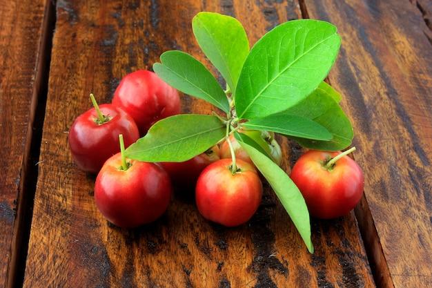 Acerola cereja crua, fresca, na mesa de madeira rústica, alta vitamina c e frutas antioxidantes