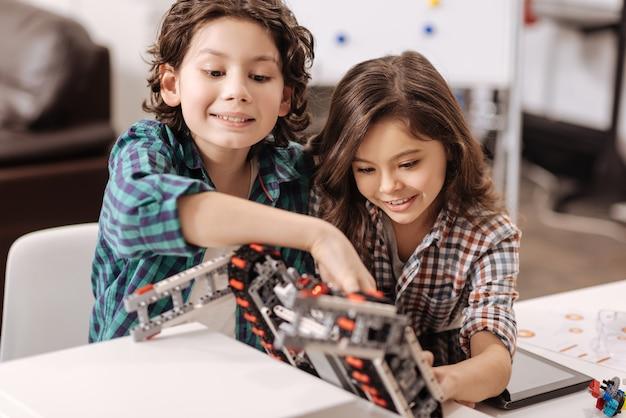 Acessando tecnologias modernas. divertiram crianças curiosas e positivas sentadas na sala de aula de ciências e usando gadgets e dispositivos enquanto expressavam alegria