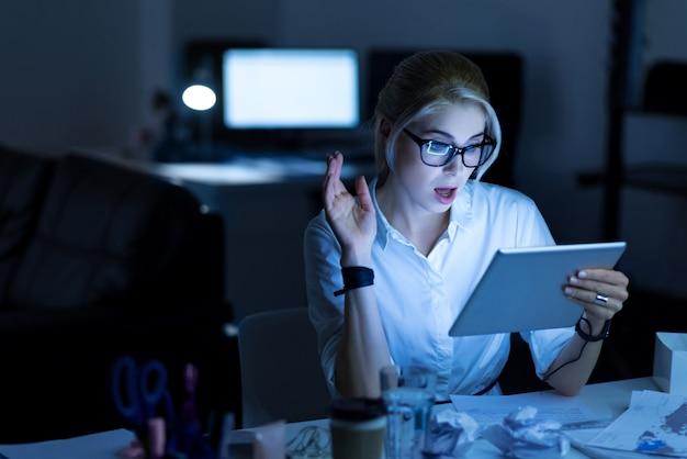 Acessibilidades surpreendentes. jovem programador habilidoso espantado sentado no escritório usando o tablet enquanto trabalhava no projeto e expressava interesse