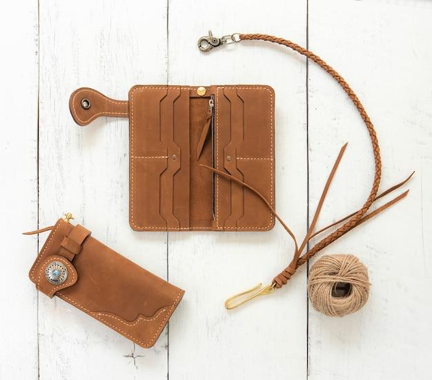 Acessório das carteiras do couro genuíno de brown isolado no fundo de madeira. vista do topo.