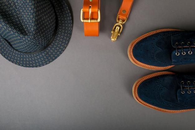 Acessório de homens, roupa. chapéu fedora preto, cinto marrom, sapatos de camurça sobre o fundo cinza.