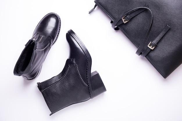 Acessório de mulher. botas pretas elegantes, bolsa de couro preta de luxo. vista do topo. postura plana.